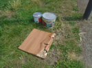 Piece of laminate flooring and tubs of paint